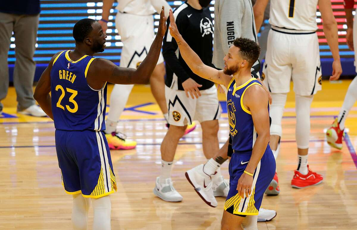 SAN FRANCISCO, CALIFORNIA - APRIL 12: Stephen Curry #30 and Draymond Green #23 of the Golden State Warriors congratulate one another during their game against the Denver Nuggets at Chase Center on April 12, 2021 in San Francisco, California. NOTE TO USER: User expressly acknowledges and agrees that, by downloading and or using this photograph, User is consenting to the terms and conditions of the Getty Images License Agreement. (Photo by Ezra Shaw/Getty Images)