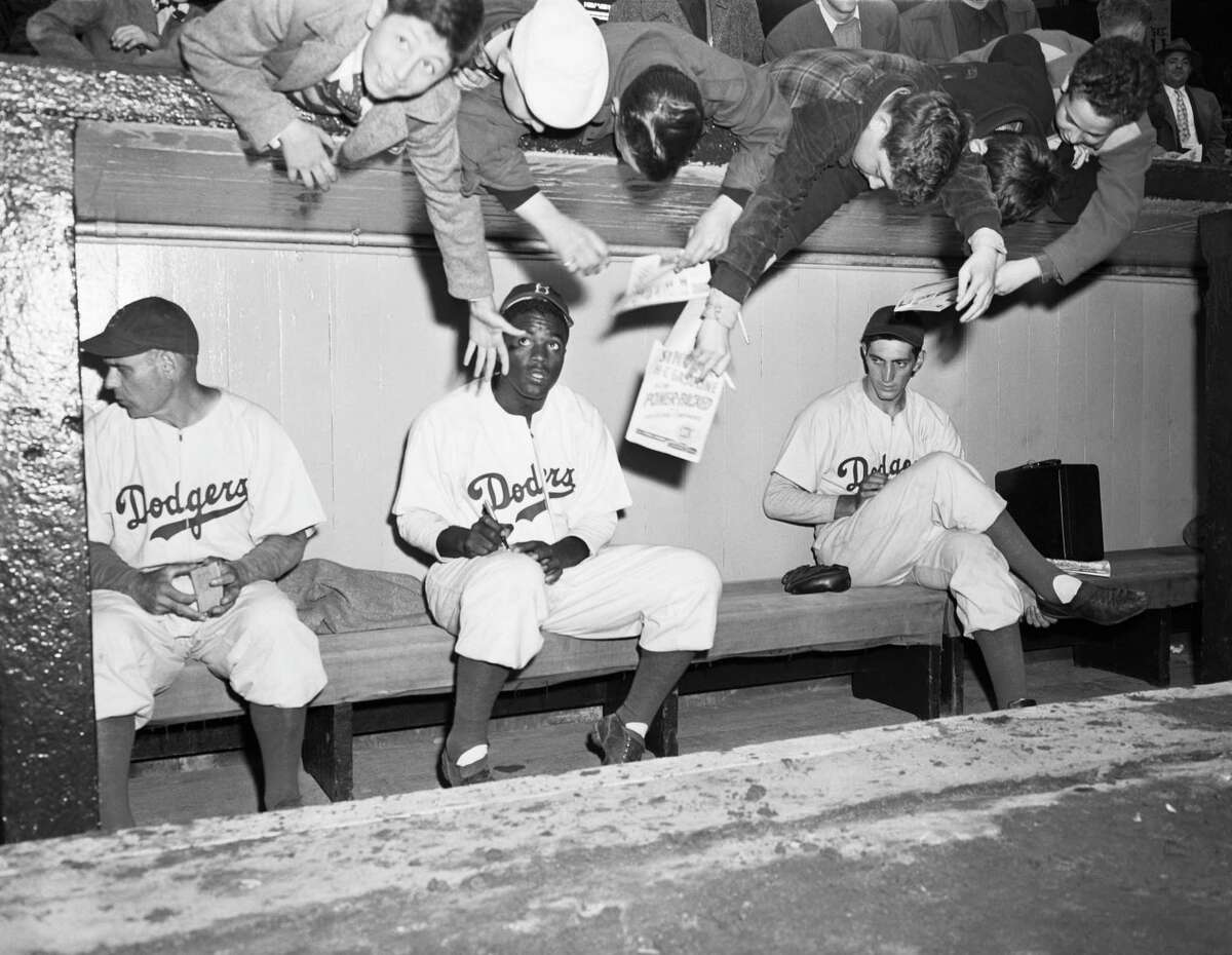 Brooklyn Dodgers fans, reach over from behind the dugout at Ebbets field trying to get an autograph from Jackie Robinson.