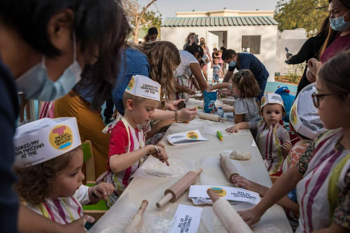 In Dubai in the United Arab Emirates, children baked matzah at the Mini Miracles Nursery, the Emirates first certified Jewish nursery school. Matzah is the traditional unleavened flatbread integral to Passover's celebration. The nursery caters to all children, but has dedicated extra-curricular activities tailored to the community'sJewish population. This is the first year UAEs Jewish residents and visitors can celebrate Passover openly since the signing of the US-brokered Abraham Accords, with large communal Passover Seders with certified Kosher food. Its another historic first for the UAE's growing Jewish community. Since the signing of the Abraham Accords in September 2020, which normalized diplomatic relations between Israel and four Muslim-majority countries Morocco, Sudan, Bahrain, and the United Arab Emirates the pace of change for Jewish life in the UAE has been dramatic. The Emirates have seen a boom in Jewish and Israeli tourism and the local Jewish community, which has been quietly emerging for years, is thriving. (Photo by Andrea DiCenzo/Getty Images)