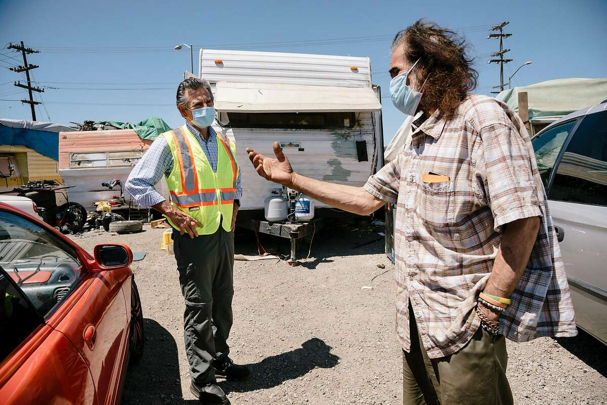 Oakland City Council Member Noel Gallo talks with Gilberto Gonzales at the High Street homeless encampment.