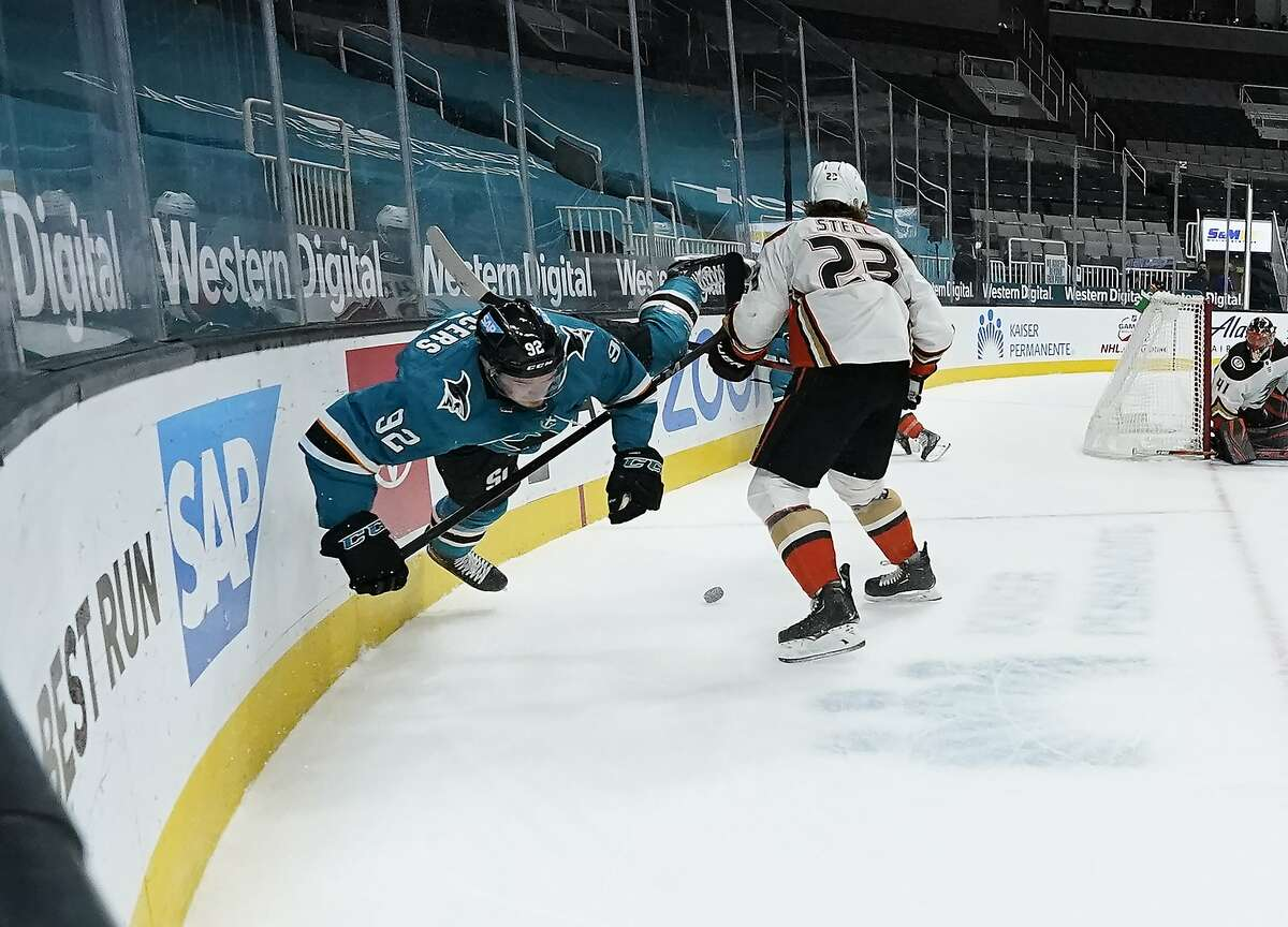 Sharks left wing Rudolfs Balcers (92) is sent flying after being checked against the boards by Ducks center Sam Steel (23) during the first period of Anaheim's win at SAP Center.