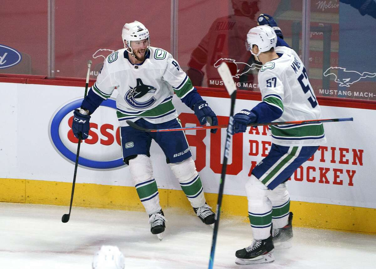 Vancouver Canucks' J.T. Miller, left, celebrates his overtime goal against the Montreal Canadiens with Tyler Myers in an NHL hockey game Friday, March 19, 2021, in Montreal. (Paul Chiasson/The Canadian Press via AP)