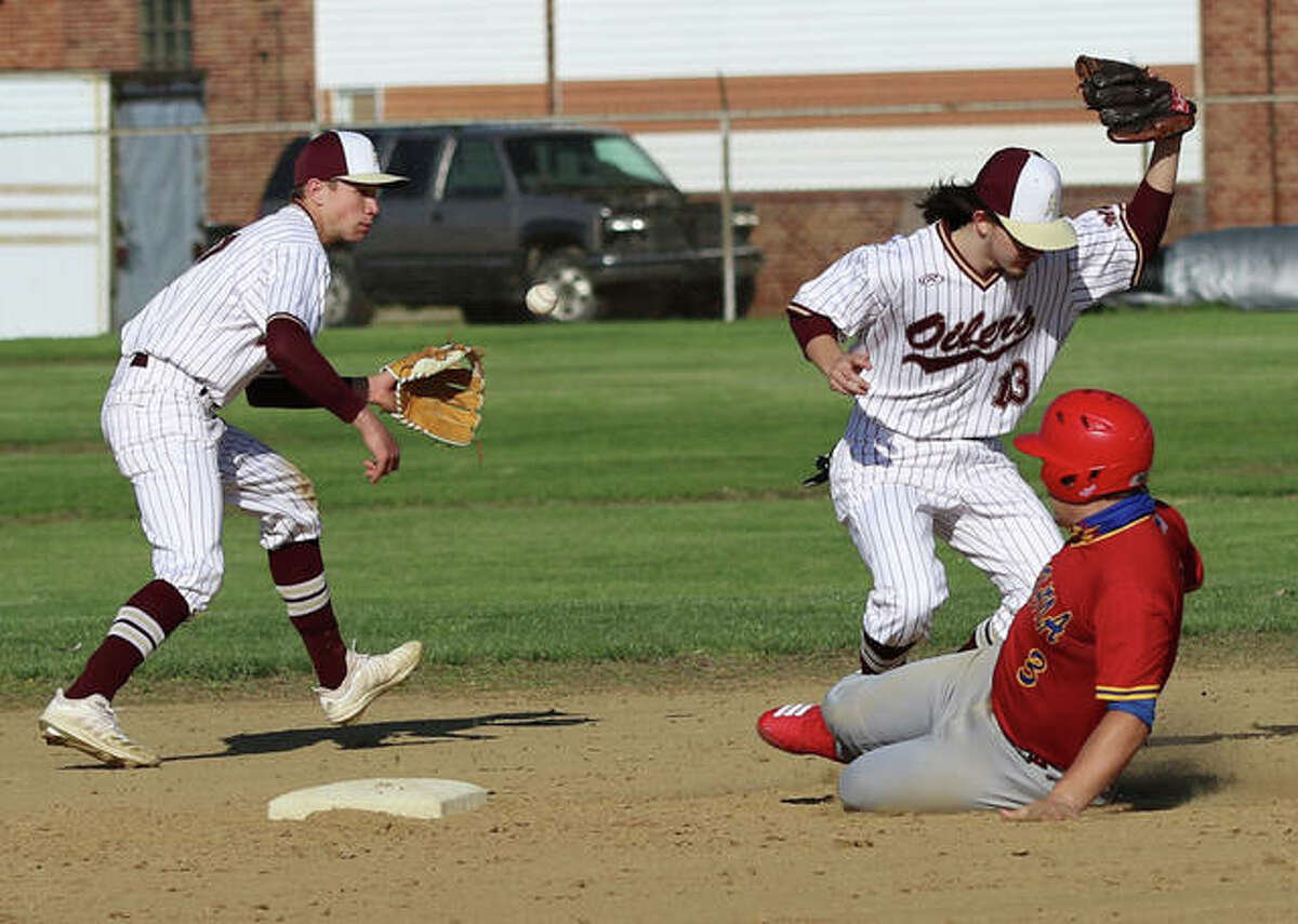 Roxana's Christian Floyd slides safely into second with a stole base as the throw skips past Oilers shortstop Seth Slayden (left) after getting past second baseman Clayton McCauley on Wednesday in Wood River.