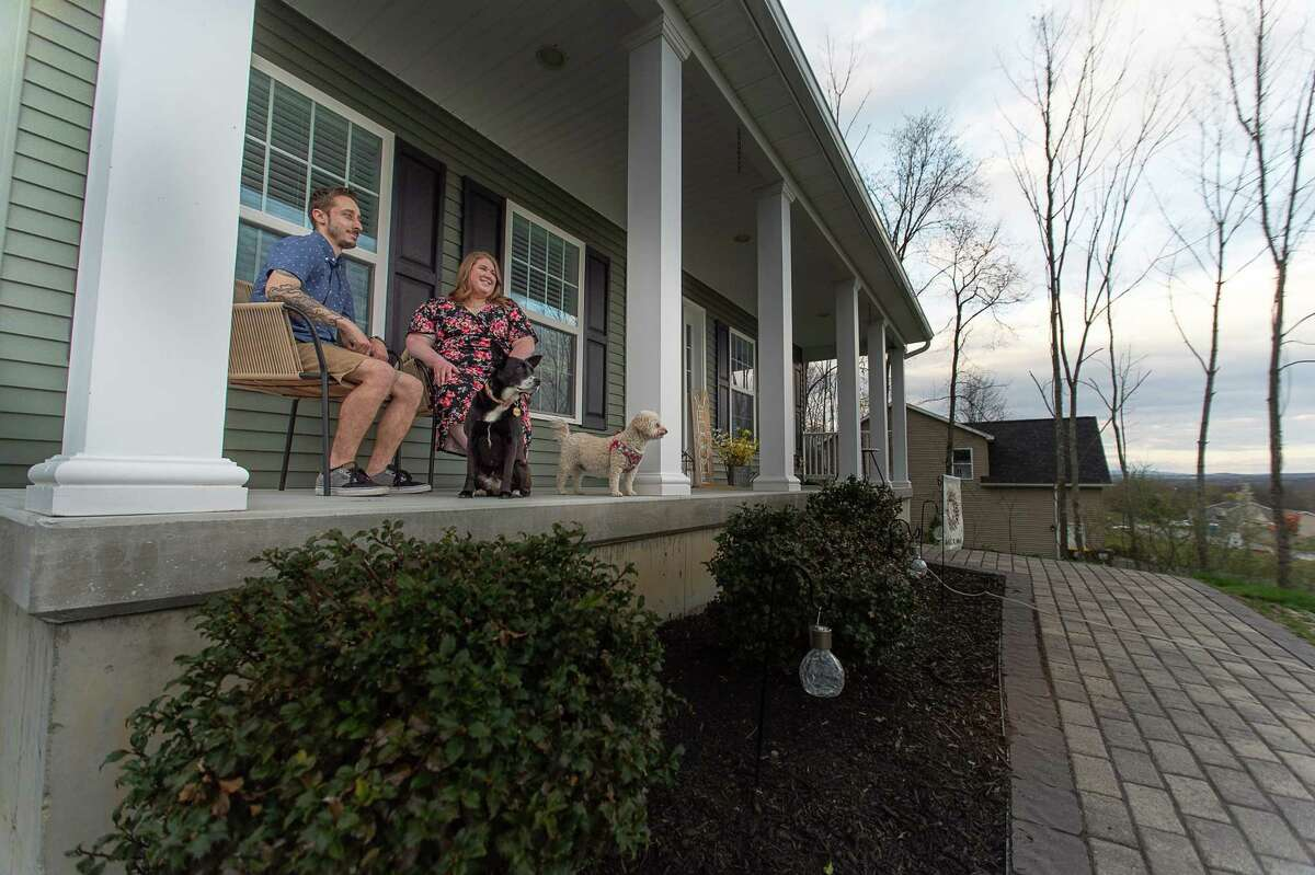 Bradley and Melissa Belanger sit outside their Stillwater home Wednesday evening with their dogs, Callie and Rosy, Apr. 14, 2021. (Jenn March, Special to the Times Union)
