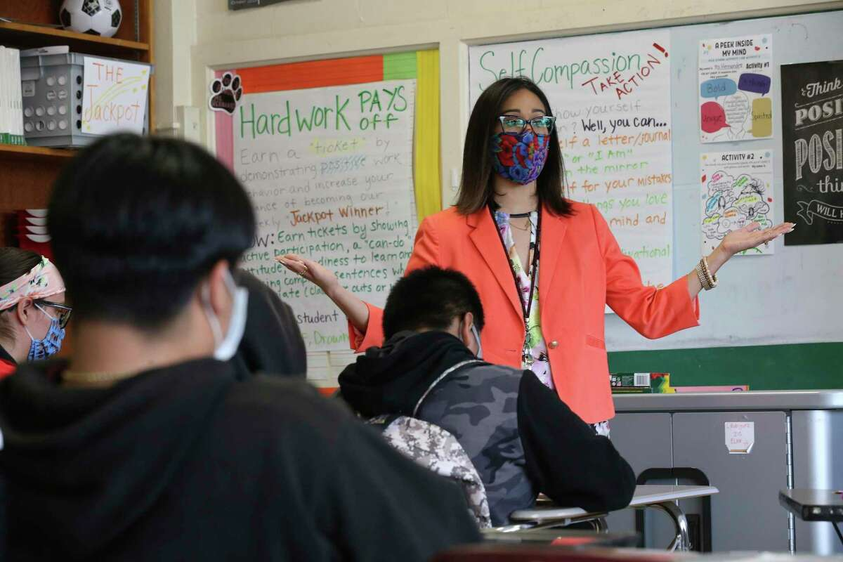 Christina Hernandez teaches a writing class to students in her classroom at Rhodes Middle School as well as those attending remotely Wednesday. About half of San Antonio ISD students are still learning remotely.