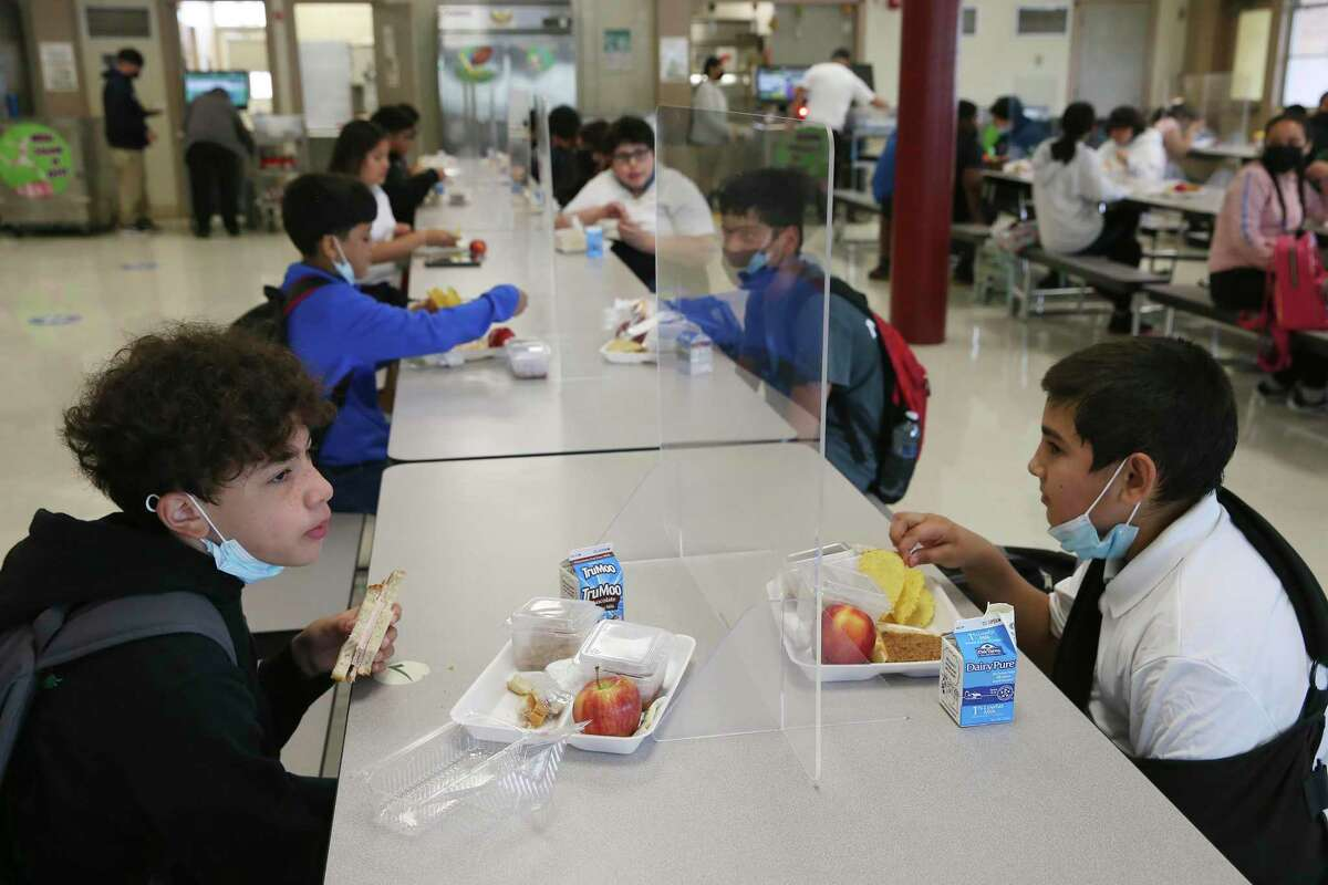 Students sit in pairs separated by plexiglass while eating lunch at Rhodes Middle School this spring. Several San Antonio school districts will offer free meals to all students during the upcoming school year.