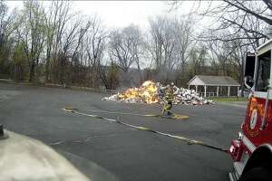 Bethel firefighters work to extinguish a fire Thursday morning that started inside a garbage truck.
