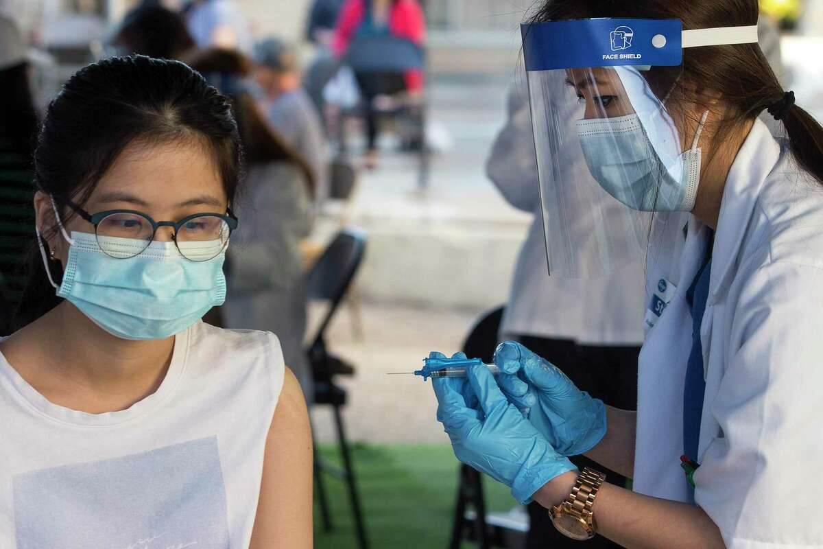 The Dang, left, gets the Johnson & Johnson vaccine from Kroger pharmacist Stephanie Phan at Thái Xuân Village condominiums Sunday.