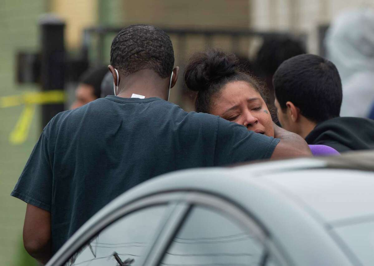 People are overcome with emotion while gathering outside an apartment complex on the 8500 block of Broadway Street where multiple agency authorities are investigating a double homicide scene that two Black males were found dead inside a vehicle Thursday, April 15, 2021, in Houston. Houston Police Department Assistant Chief Ben Tien said sveral cars boxed the victims' vehicle and a group of people jumped out of the cars and shot at the victims before they took off.