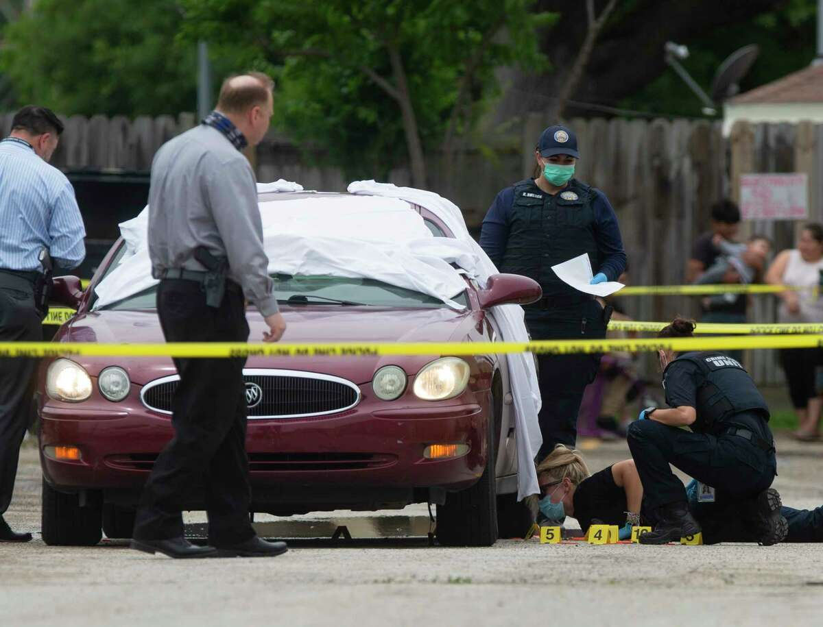 Multiple agency authorities investigate a double homicide scene where two Black males were found dead inside a vehicle at an apartment complex on the 8500 block of Broadway Street Thursday, April 15, 2021, in Houston. Houston Police Department Assistant Chief Ben Tien said sveral cars boxed the victims' vehicle and a group of people jumped out of the cars and shot at the victims before they took off.