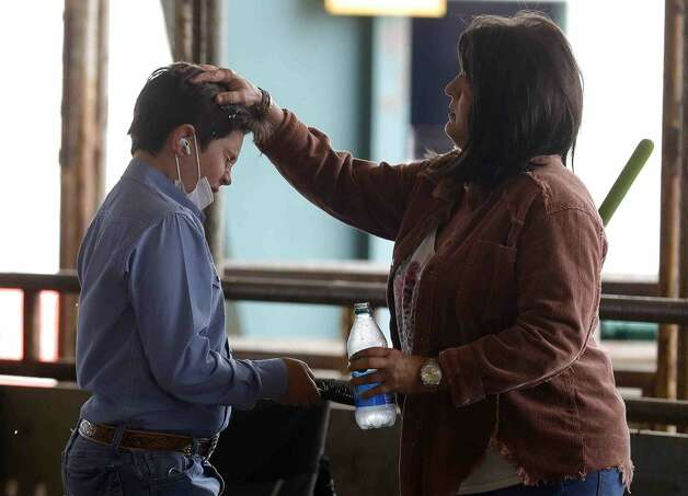 Heath Graves of Montgomery Jr FFA reacts as his mother, Wendy, uses water her drink to smooth out his hair before the replacement heifer show at the Montgomery County Fair & Rodeo, Thursday, April 15, 2021, in Conroe. Photo: Jason Fochtman/Staff Photographer / 2021 ? Houston Chronicle