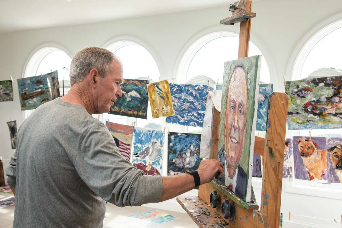 Former President George W. Bush paints a portrait in his studio.
