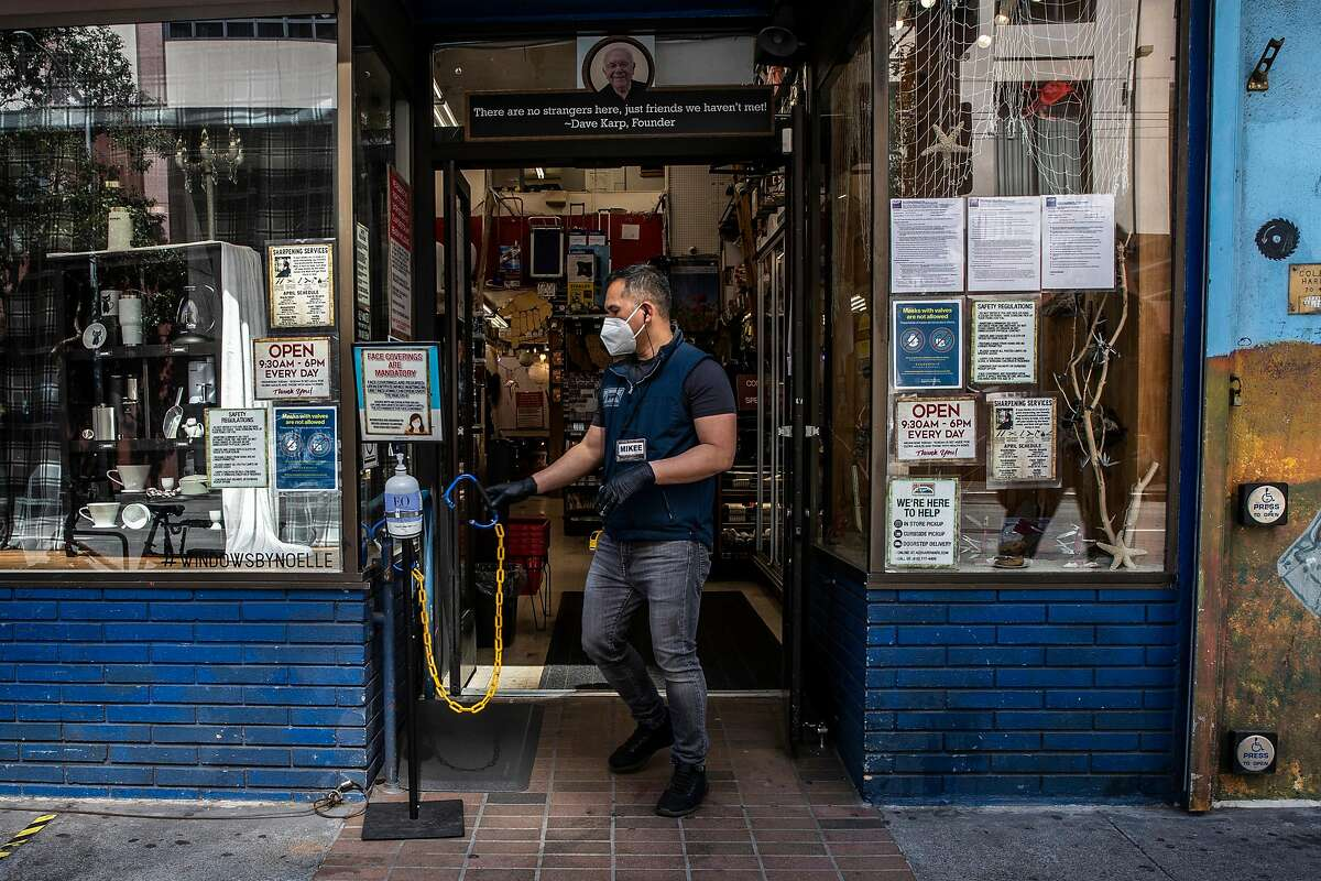 Michael Garde moves a chain at the entrance to limit the number of customers amid the ongoing COVID-19 pandemic at Cole Hardware in Downtown San Francisco, California Wednesday, April 14, 2021.