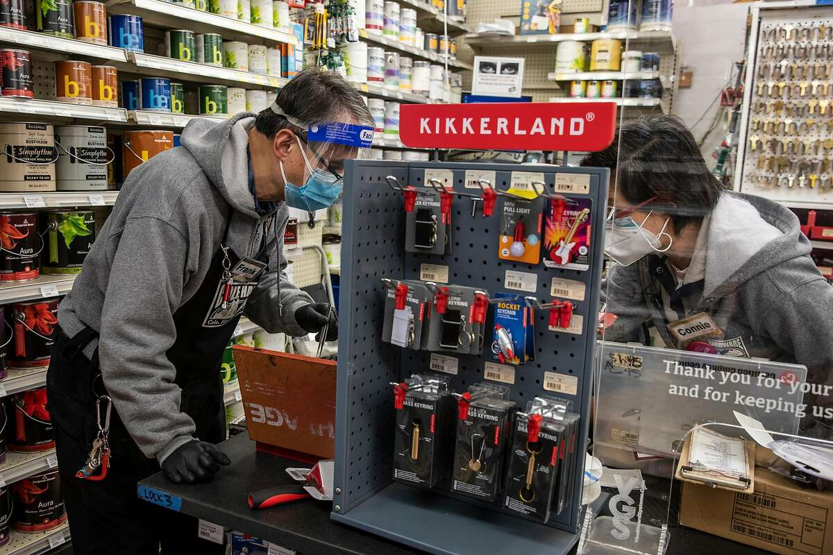 (L-R) Master Locksmith Frank Yee, Joseph Mondejar and Assistant Manager Connie Zhang look for a part while rekeying a lock at Cole Hardware in Downtown San Francisco, California Wednesday, April 14, 2021.