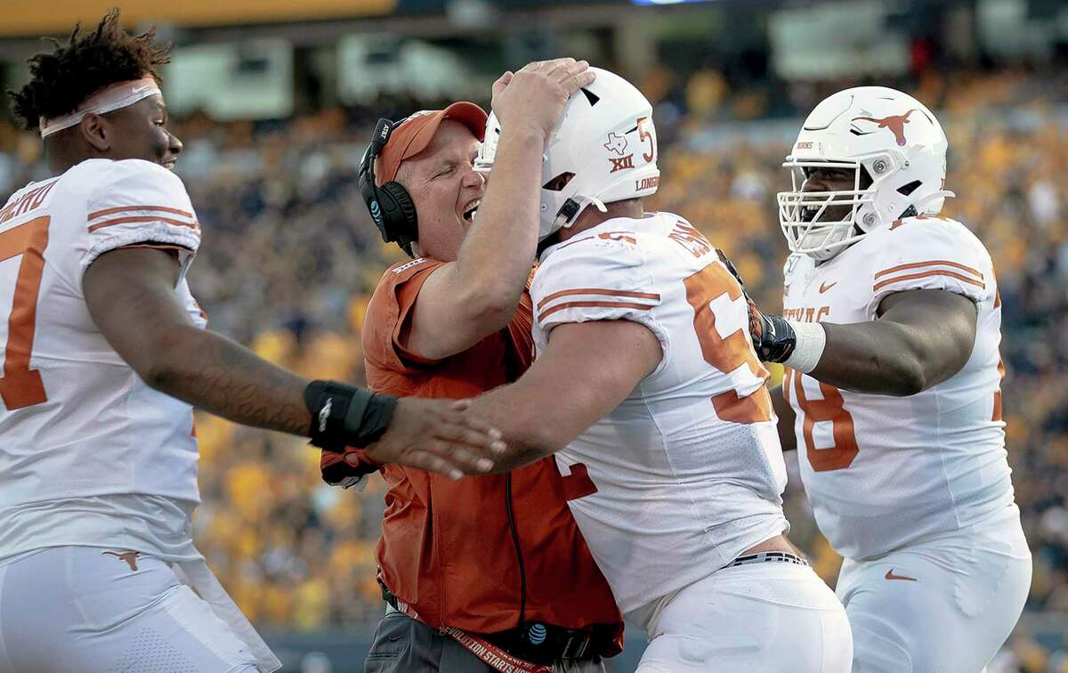 Texas lineman Samuel Cosmi (52) celebrates a touchdown with offensive line coach Herb Hand, center left, during an NCAA football game against West Virginia, Saturday, Oct. 5, 2019, in Morgantown, W. Va. (Nick Wagner/Austin American-Statesman via AP)