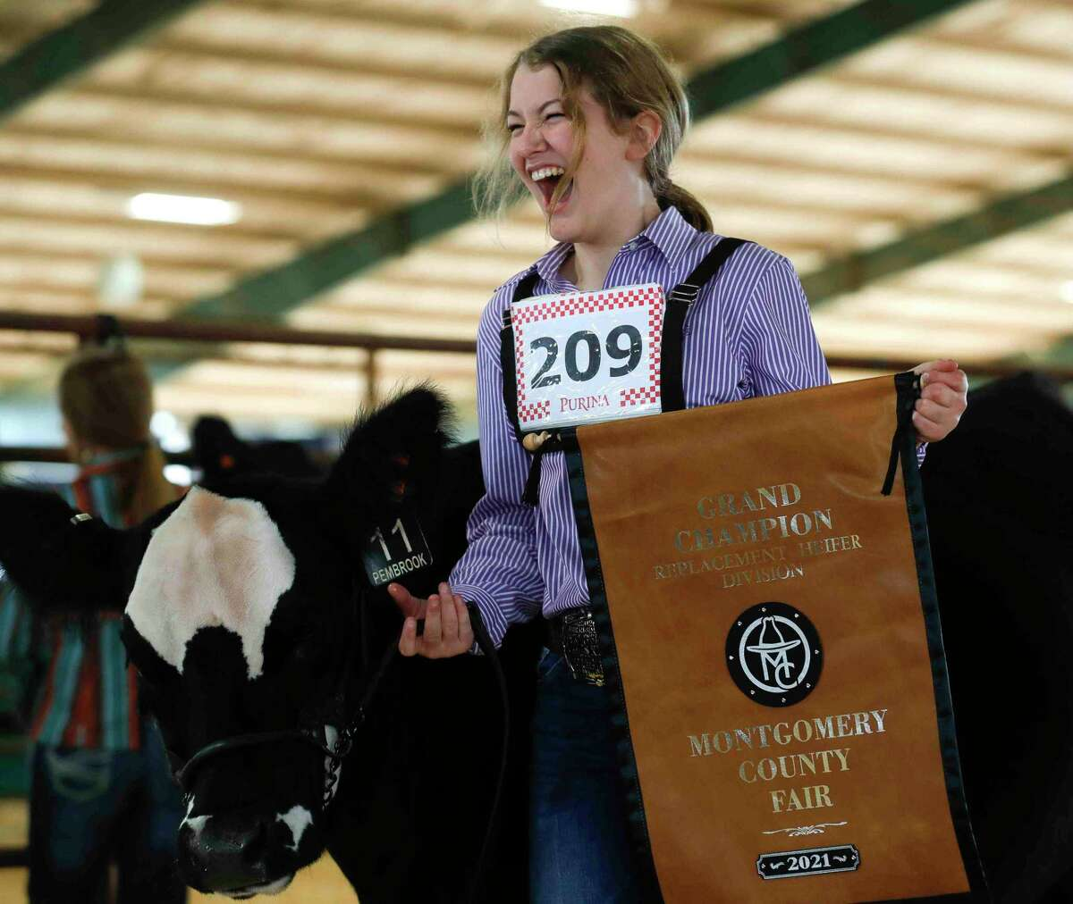 Zoe Romanchuk of Montgomery Dobbin 4-H reacts after her heifer, Trixie Pixie, won grand champion during the replacement heifer show at the Montgomery County Fair & Rodeo, Thursday, April 15, 2021, in Conroe. Romanchuk became the third straight sibling in her family to win the replacement show.