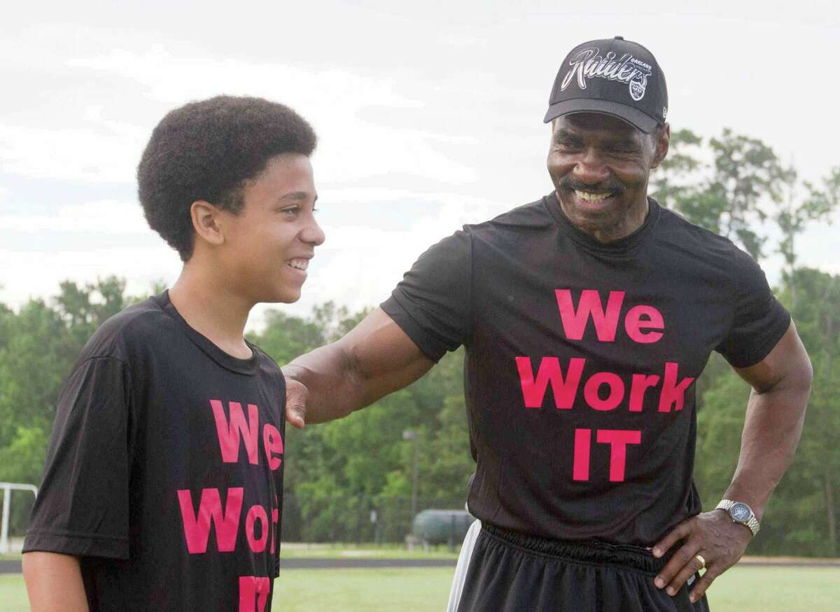 Gerald Irons Sr., a former NFL player with the Oakland Raiders, jokes with Adam Clark during the Gerald Irons Sr. Football and Leadership Development Camp at College Park High School.