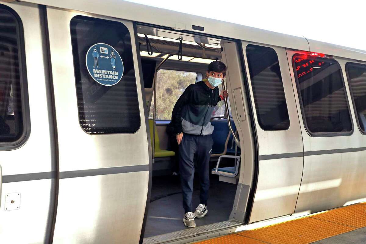 A passenger looks from a train at the BART station in Daly City, Calif., on Wednesday, April 14, 2021.