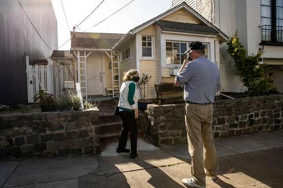 San Francisco natives Marsha and Bryan Britt stand on the sidewalk as they visit 1227 24th Avenue, a San Francisco City Landmark and a home made up of three Type A and one Type B 1906 earthquake refugee cottages after reading about its existence in San Francisco, California Wednesday, April 14, 2021.
