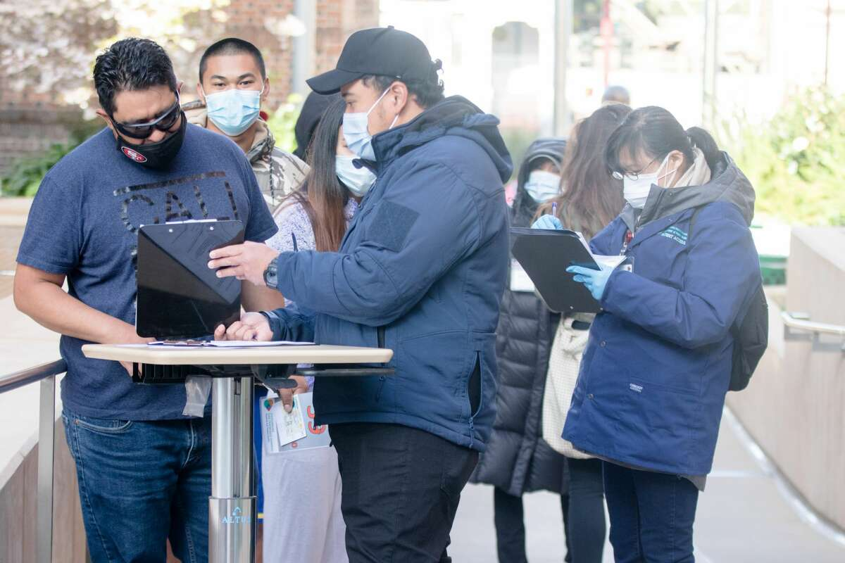 People outside Zuckerberg San Francisco General Hospital in a walk-up line sign up to receive the COVID-19 vaccine in San Francisco on April 15, 2021, the first day that anyone over 16 years old in California could receive the COVID-19 vaccine.