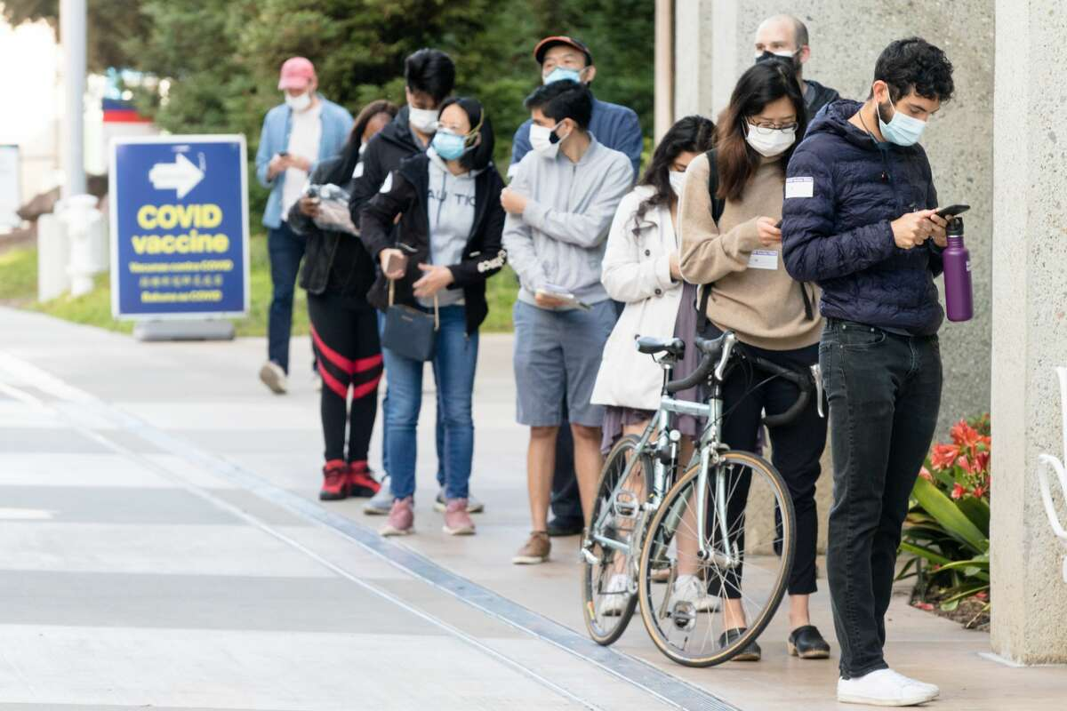 People outside Zuckerberg San Francisco General Hospital stand in a walk-up line to receive the COVID-19 vaccine in San Francisco on April 15, 2021, the first day that anyone over 16 years old in California could receive the COVID-19 vaccine.