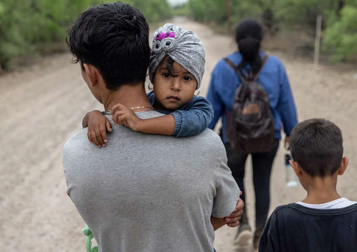 An immigrant child looks back towards Mexico after crossing the border into the United States with her family on April 14, 2021 in La Joya, Texas.