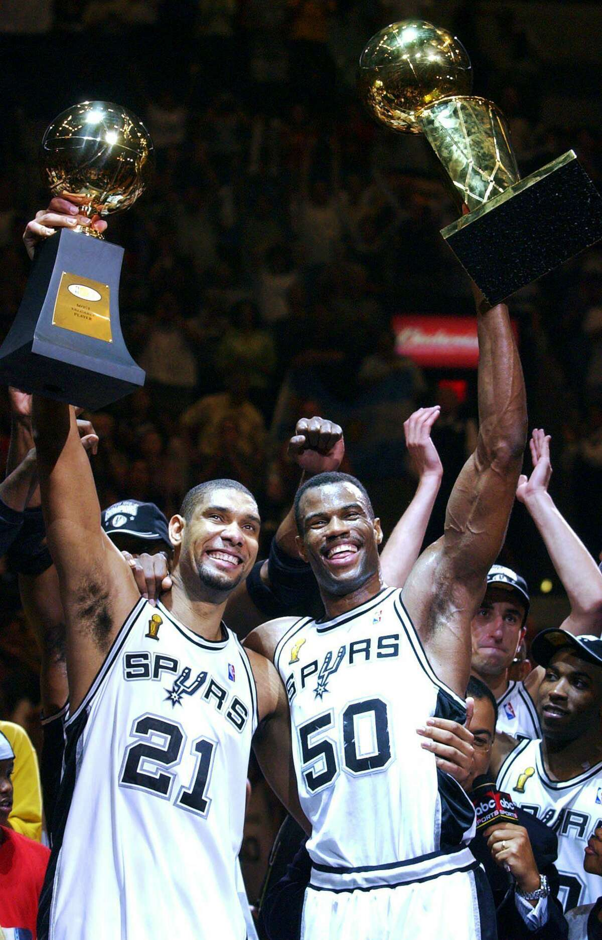 FILE - In this June 15, 2003 file photo, San Antonio Spurs players Tim Duncan (21) holds his MVP trophy while teammate David Robinson (50) holds the championship trophy after the Spurs beat the New Jersey Nets 88-77 to win the NBA Championship in Game 6 of the NBA Finals in San Antonio. Duncan announced his retirement on Monday, July 11, 2016, after 19 seasons, five championships, two MVP awards and 15 All-Star appearances. It marks the end of an era for the Spurs and the NBA. (AP Photo/Eric Gay, File)