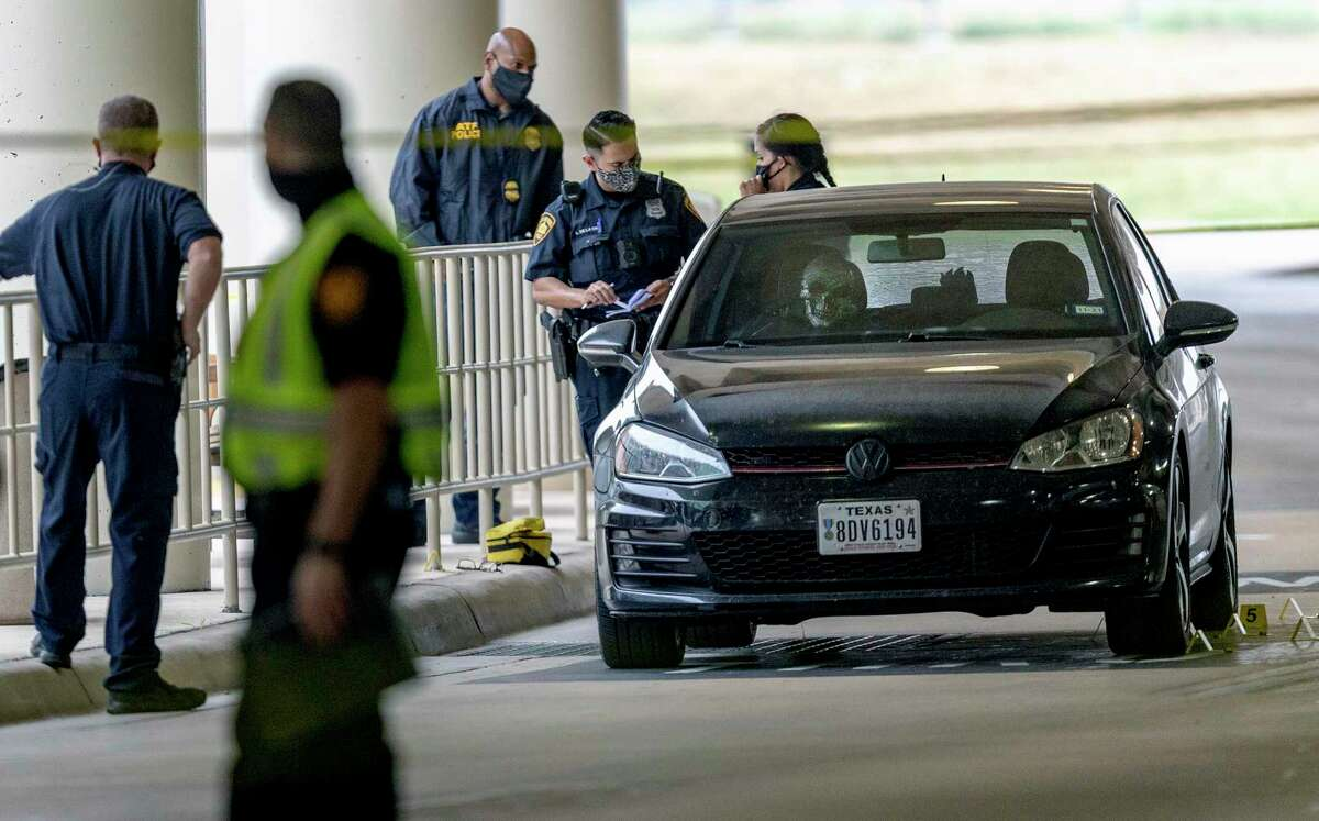 Police officers examine a vehicle Thursday afternoon April 15, 2021 at the San Antonio International Airport after an officer involved shooting there. The airport was evacuated for a time and TSA checkpoints were locked down as a precaution.
