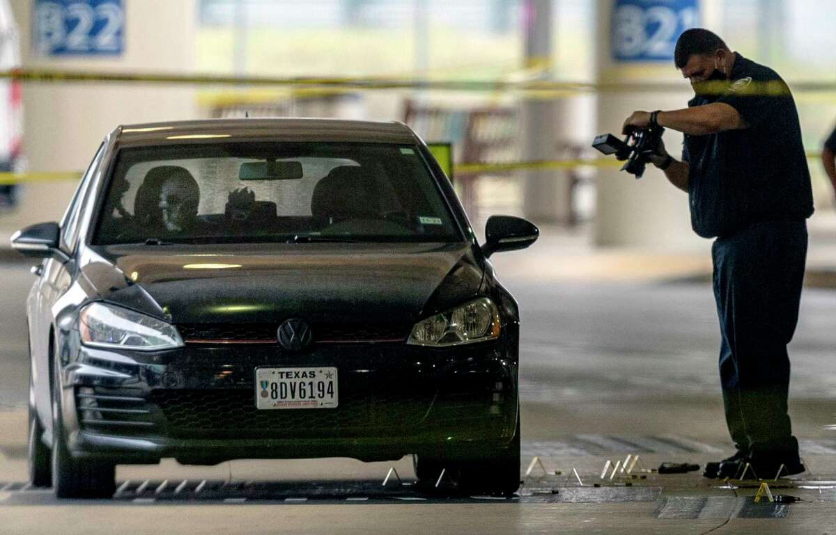 A San Antonio police department official photographs the scene Thursday, April 15, 2021 around a Volkswagen sedan with disabled veteran plates at the San Antonio International Airport after an officer-involved shooting in the passenger pick-up area of the airport terminal. What appears to be a skeleton or skeleton mask can be seen in the passenger seat of the vehicle. The shooting caused officials to evacuate the airport terminals as a precaution.