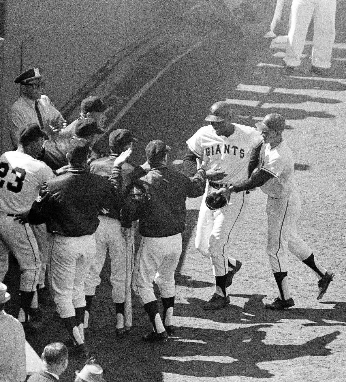 Giants' first baseman Willie McCovey is welcomed by teammates at San Francisco dugout after he drove the ball high over the right field fence in seventh inning, Oct. 5, 1962 in San Francisco and put Giants ahead, 2-0, in second game of World Series in Candlestick Park. Giants shutout the New Yorkers, 2-0. (AP Photo)
