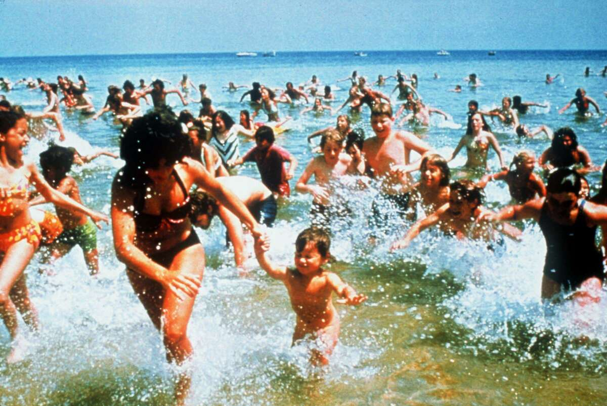 Beach-goers run from the water in a scene from the 1975 film
