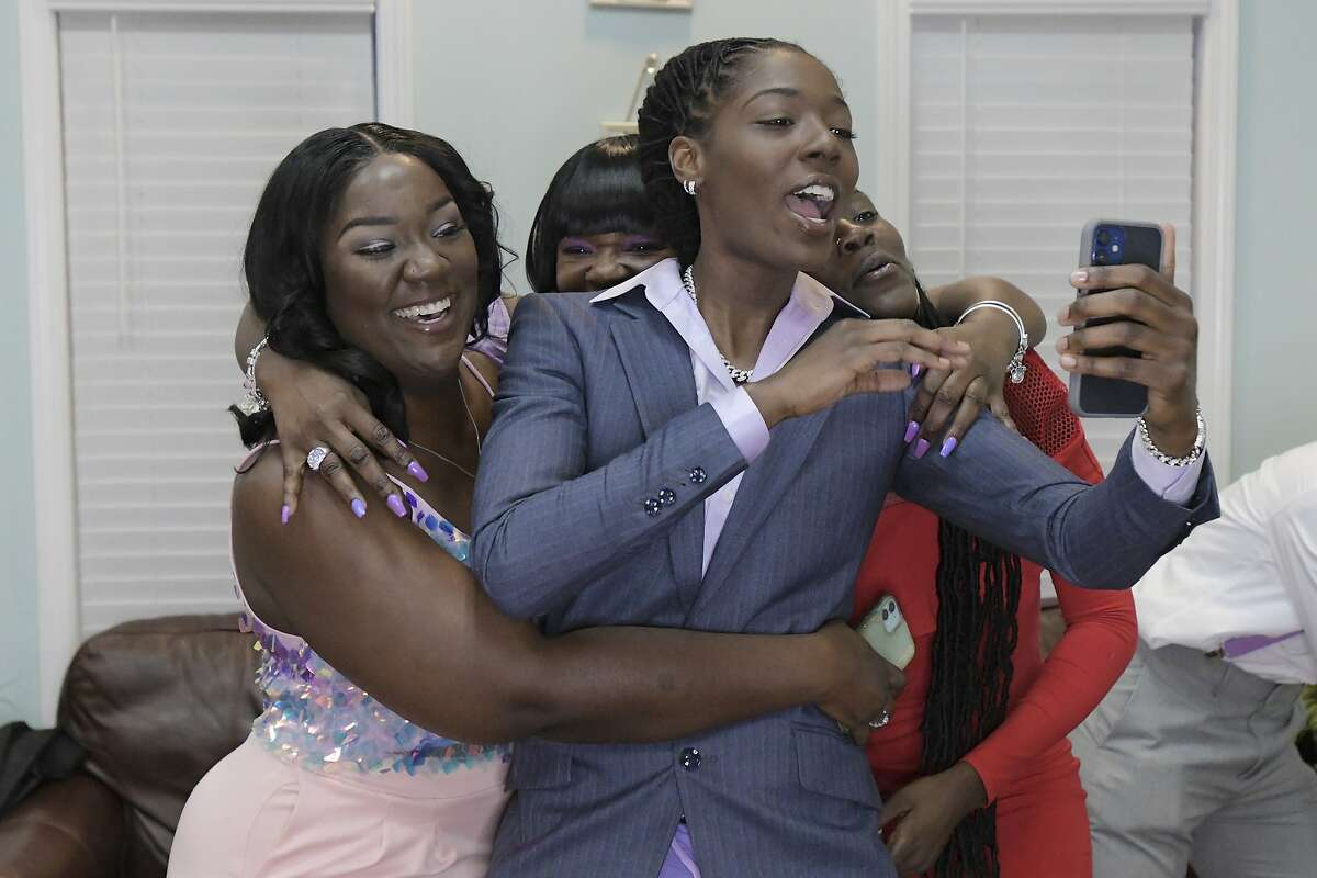 Rennia Davis, front, is hugged by sister Netta Chandler, mother Sheretta Davis and sister Shavonna Davis after Davis was selected in the WNBA basketball draft by the Minnesota Lynx, Thursday, April 15, 2021, in Jacksonville, Fla. (Bob Self/The Florida Times-Union via AP)