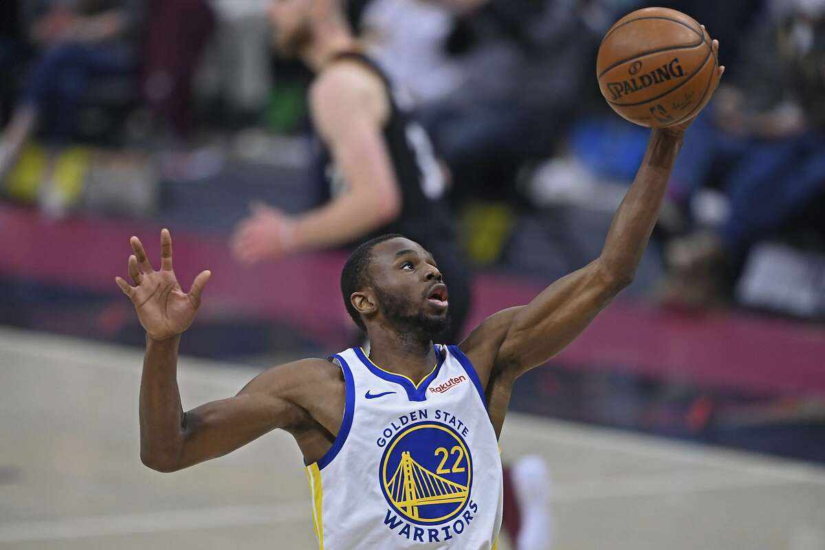 Golden State Warriors' Andrew Wiggins (22) rebounds in the first half of an NBA basketball game against the Cleveland Cavaliers, Thursday, April 15, 2021, in Cleveland. (AP Photo/David Dermer)