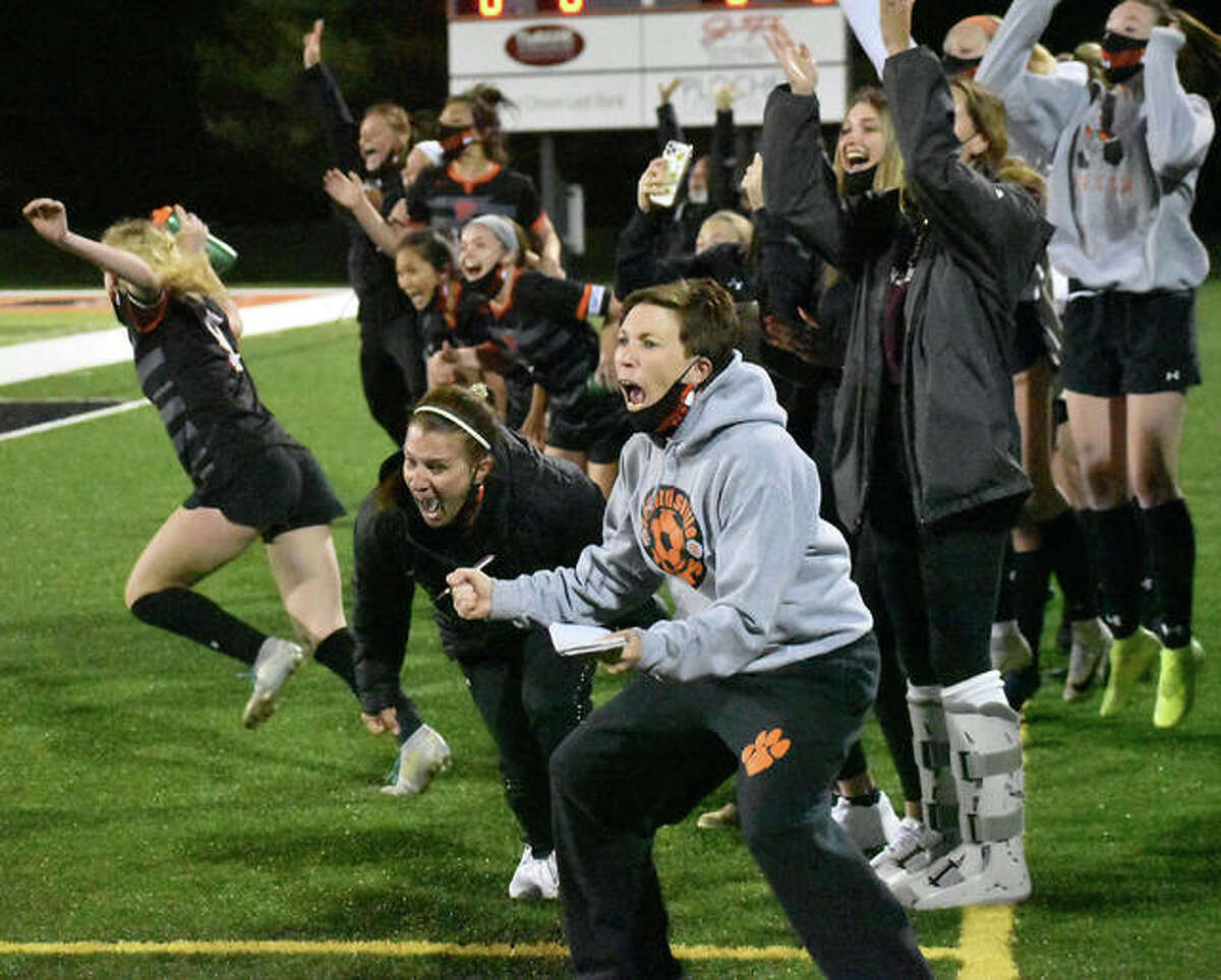 The Edwardsville girls soccer team and coaching staff erupts in celebration after a PK save made by Kaitlyn Naney to end the game against O'Fallon on Thursday inside the District 7 Sports Complex.