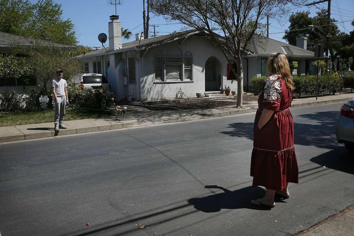 Brandi Moody talks with neighbor Scott Fulton across the street from her home in San Jose.