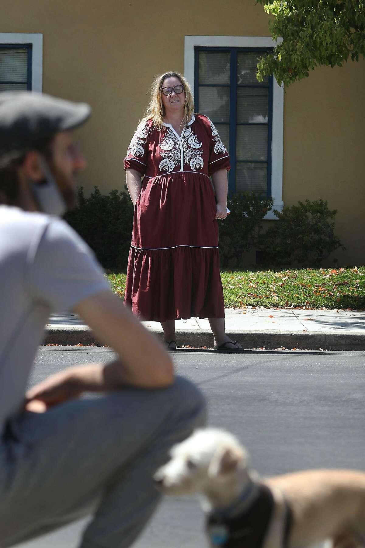 Brandi Moody talks with her neighbor Scott Fulton as he walks Herbie in their San Jose neighborhood.