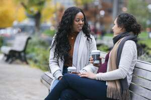 A pregnant Eurasian woman is spending time with her black friend outdoors. The multi-ethnic pair of women are enjoying a relaxing afternoon together in a park. They are sitting on a park bench while talking and drinking coffee.