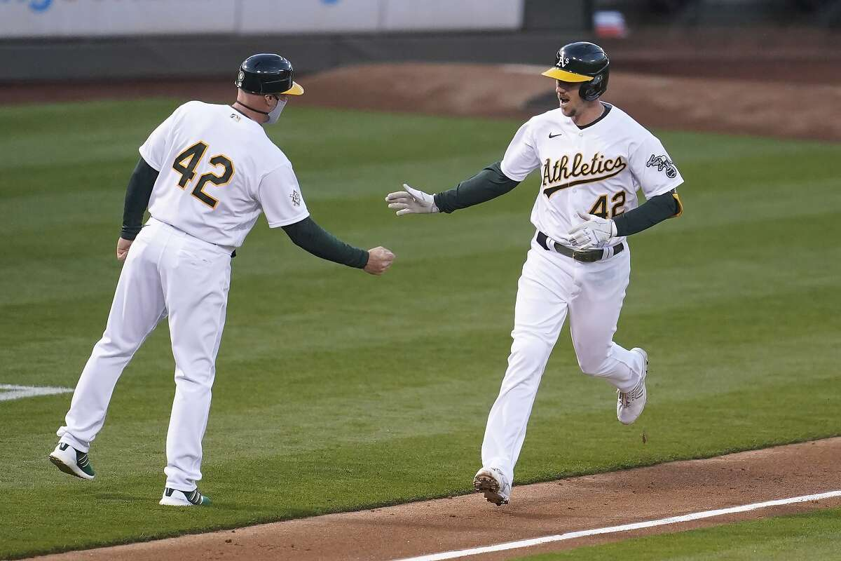 Oakland Athletics' Stephen Piscotty, right, is congratulated by third base coach Mark Kotsay after hitting a solo home run against the Detroit Tigers during the third inning of a baseball game in Oakland, Calif., Thursday, April 15, 2021. (AP Photo/Jeff Chiu)