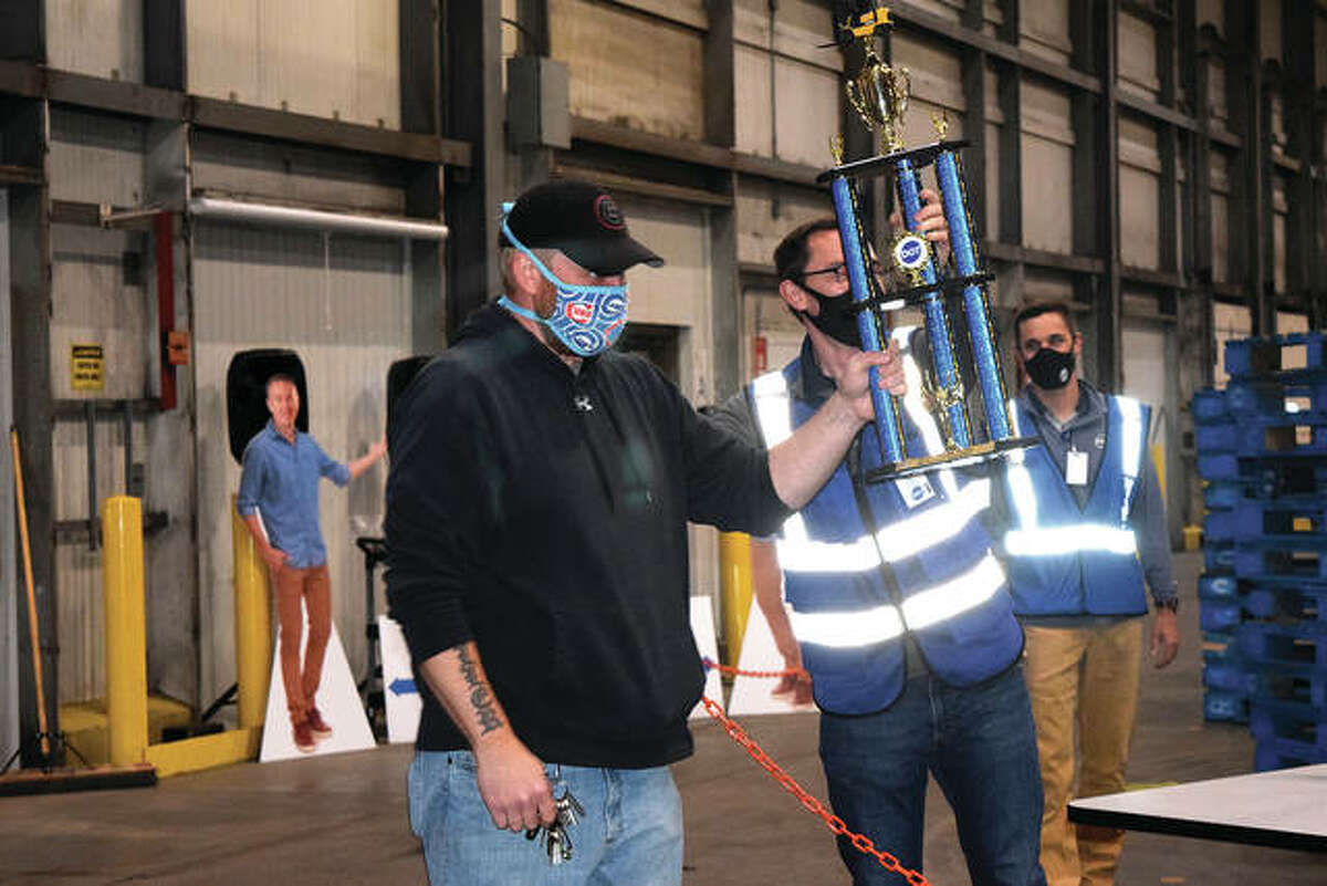 John Bordewick (right), general manager of Dot Foods in Mount Sterling, awards a trophy Thursday during the company's Forklift Rodeo.