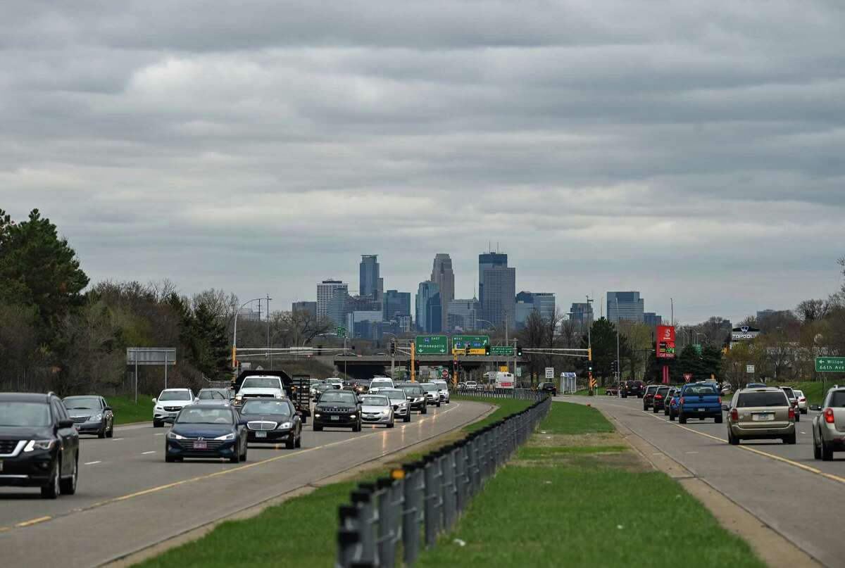 Traffic moves along Highway 252 in Brooklyn Center as the Minneapolis skyline stands in the background.