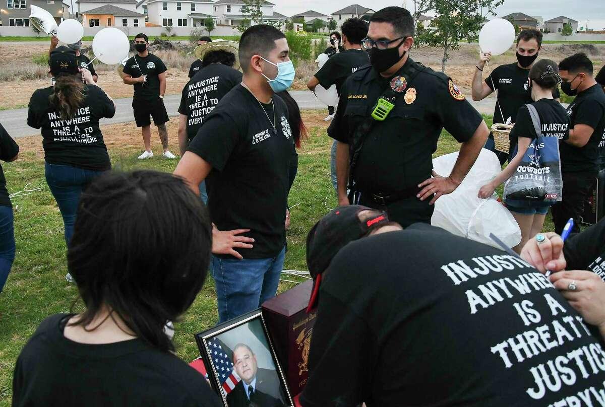 Firefighter Joe Lopez Jr. consoles John De Luna during a vigil for Guadalupe David De Luna on the anniversary of his death, Thursday, Apr. 15, 2021, at Devine Mercy Park.