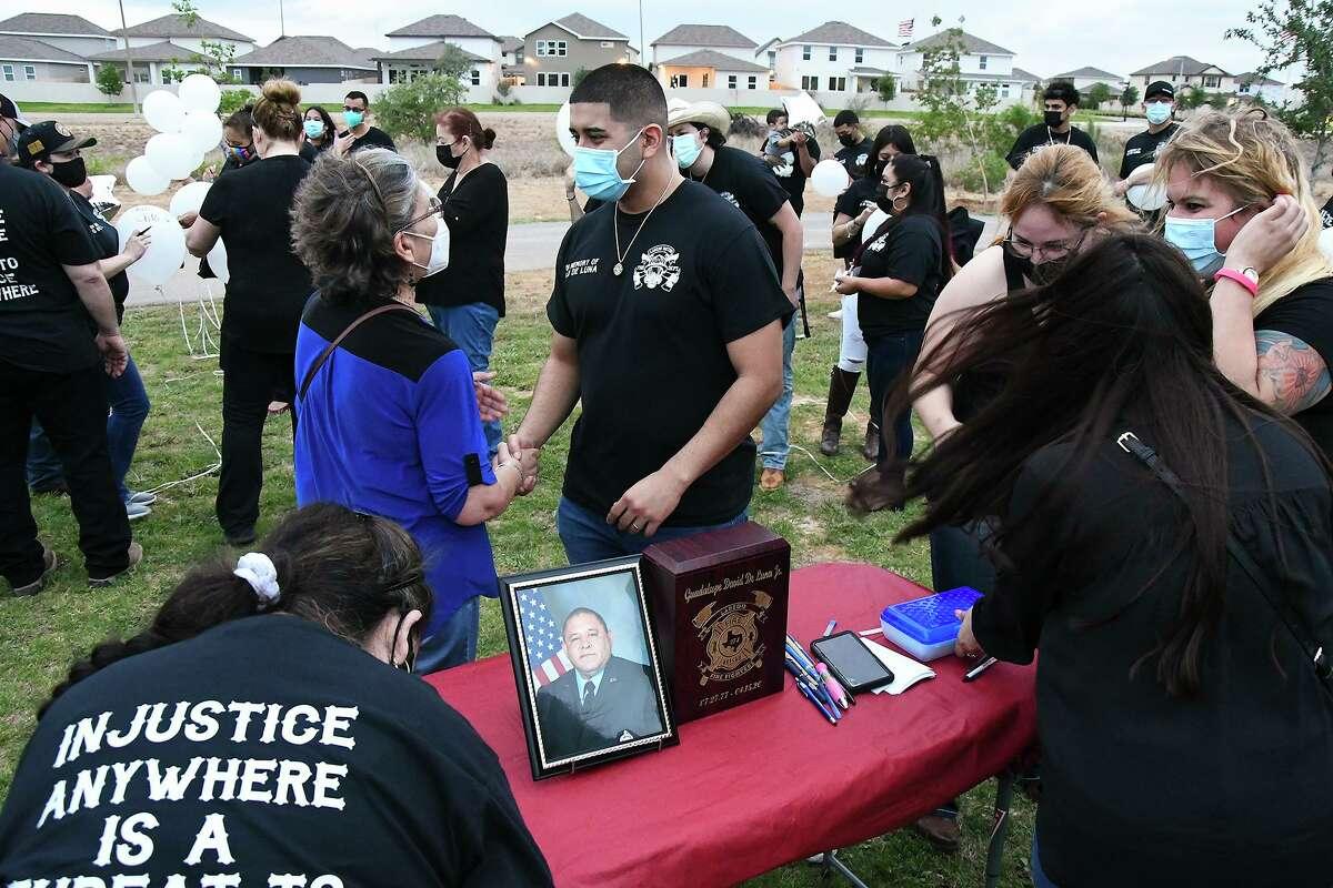 A close family friend, Margarita Martinez, gives her condolences to John De Luna, the late Guadalupe David De Luna Jr.'s eldest son, Thursday, Apr. 15, 2021 at Devine Mercy Park during a vigil for the late De Luna Jr.