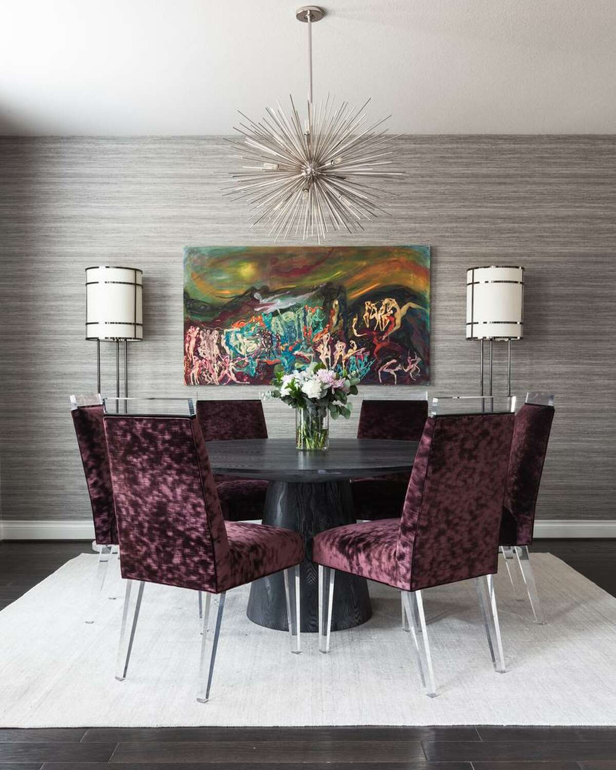 The showstopper dining room has faux grasscloth vinyl wallpaper, a chrome starburst chandelier and custom dining chairs covered in purple couture velvet and finished with acrylic legs.
