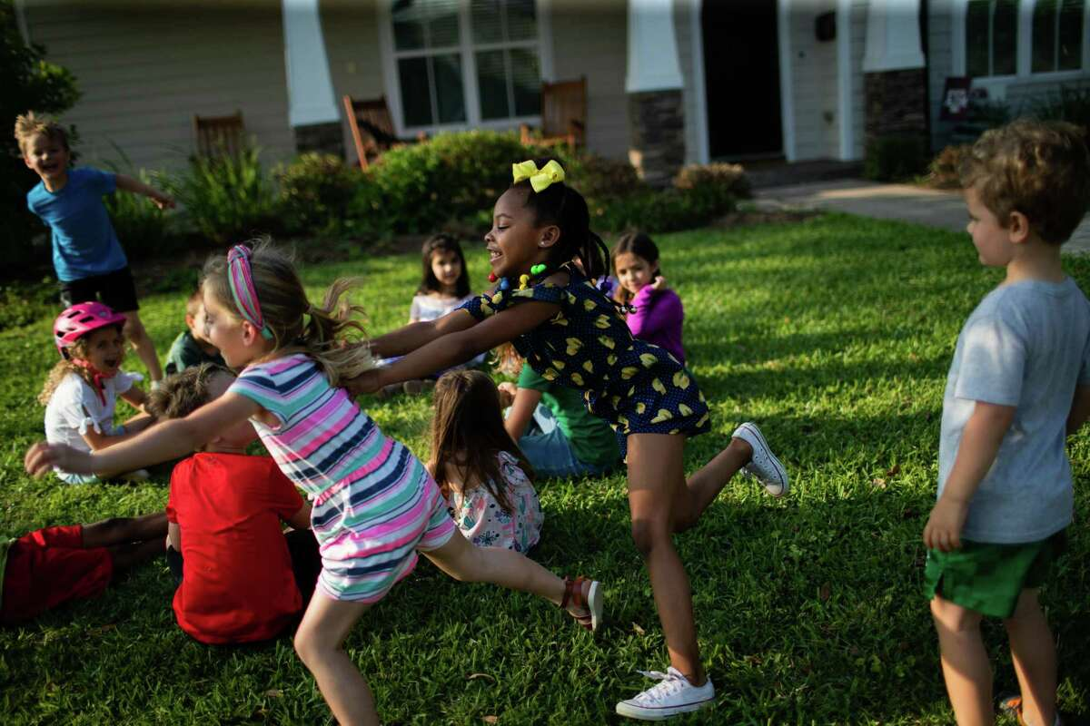 Oak Forest resident Julia Jackson, 5, plays duck duck goose with her neighbors, Monday, April 12, 2021, in Houston.