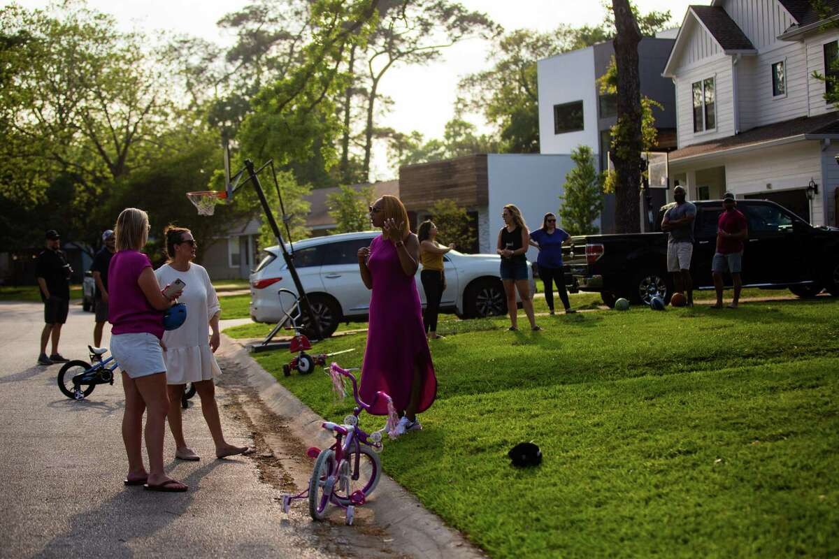 Oak Forest neighbors enjoy the afternoon together at their street, Monday, April 12, 2021, in Houston.