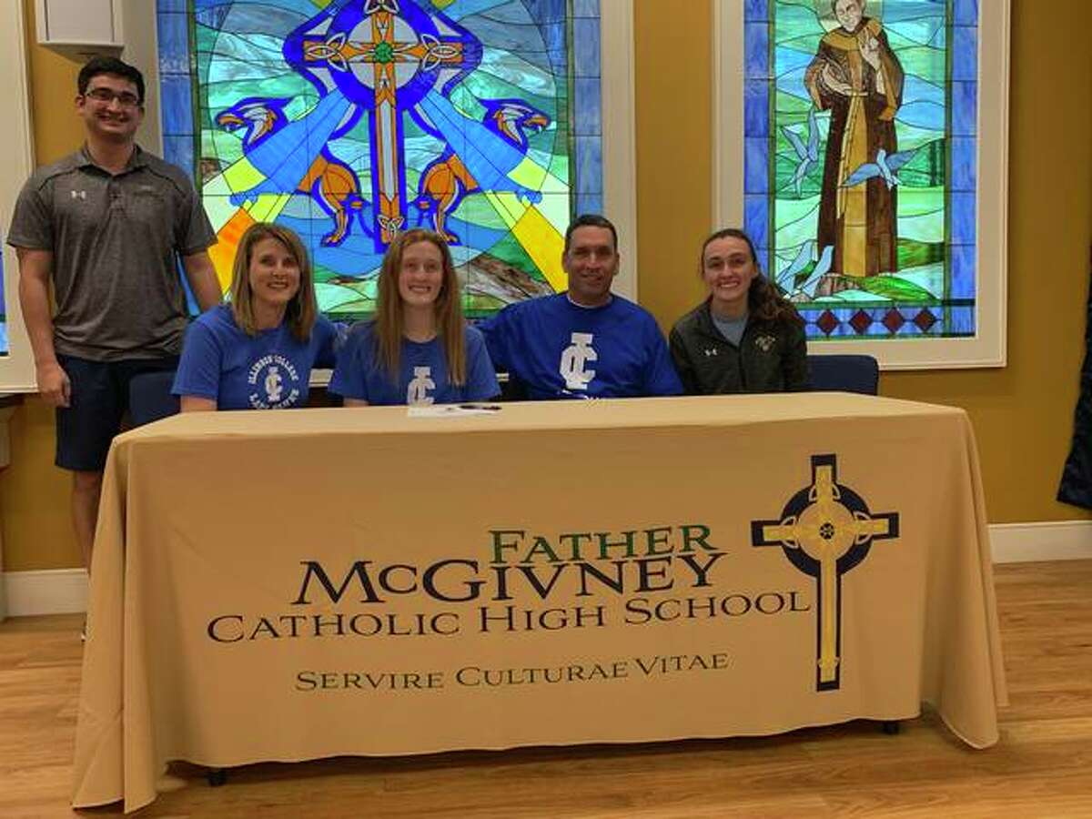 Father McGivney senior Anna McKee, seated third from right, will play college basketball for Illinois College in Jacksonville. She is joined in the picture by her family and coach Jeff Oller.