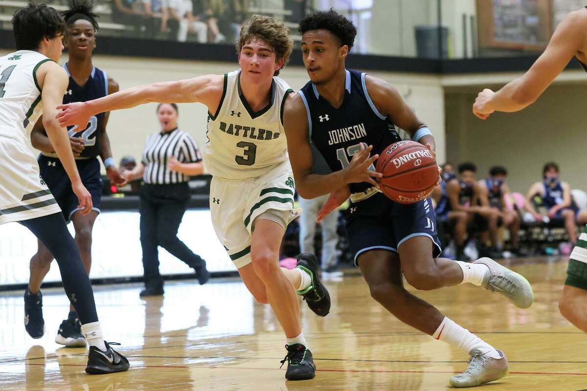 Johnson's Kendall Dow, right, drives to the basket as Reagan's Trey Thompson defends during their District 28-6A boys basketball game at Littleton Gym on Saturday, Jan. 23, 2021. Johnson beat Reagan 66-46.