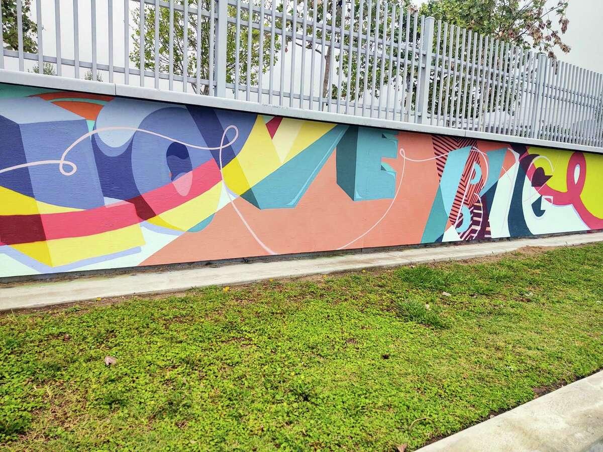 "Artist Gabriel Prusmack began his mural on the walls of the Lee and Joe Jamail Skatepark by writing the words ""love big"""