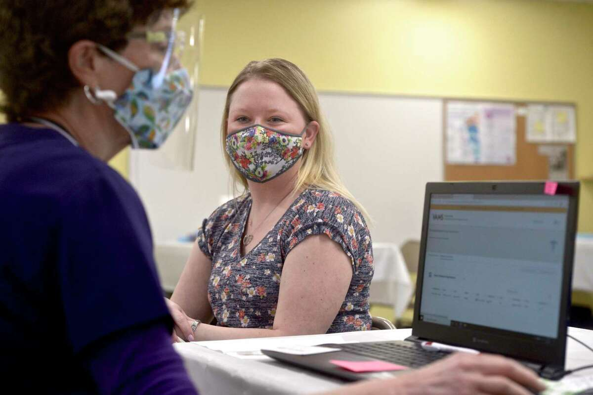 Jennifer Barabas, of Brookfield, has her information taken down by pharmacist Kathy Haddy before she receives her first dose of COVID-19 vaccine at the new location of the Brookfield clinic. The clinic is set up in the old St Joseph Catholic Academy. Wednesday, April 8, 2021, in Brookfield, Conn.