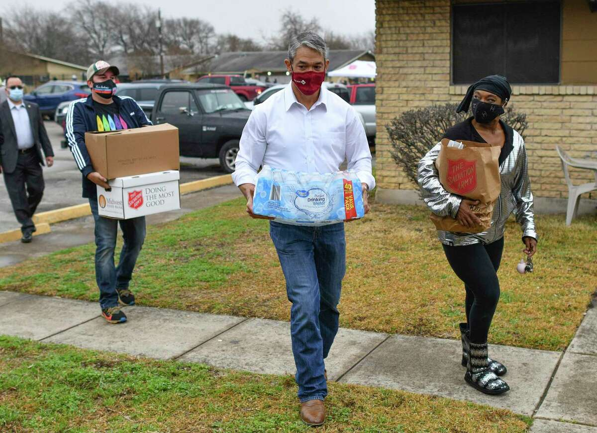 Stephanie Sacker, right, gets help from Mayor Ron Nirenberg, who carries donated water to her apartment on Thursday, Feb. 25, 2021. Emergency food boxes and bottled water were handed out to the residents of the Arbors on Rustleaf. Councilwoman Adriana Rocha Garcia partnered with the Salvation Army to set up the distribution effort in the wake of last week's utility outages due to the effects of subfreezing weather.